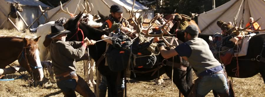 Photo of hunters securing antlers to pack animals